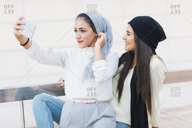 Young Muslim women taking selfies