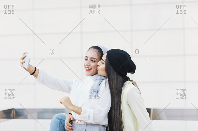 Young Muslim women kissing and taking selfies