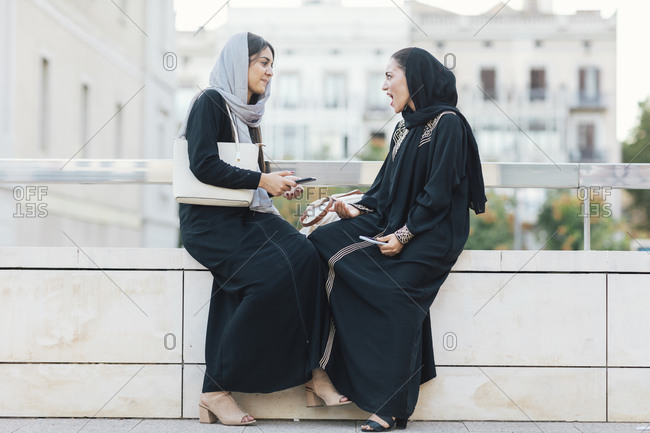 Two young Muslim women in burqas talking on city street