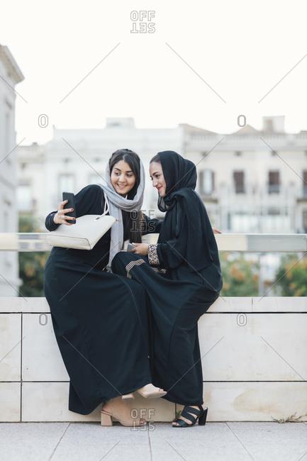 Young Muslim women wearing burqas taking selfies