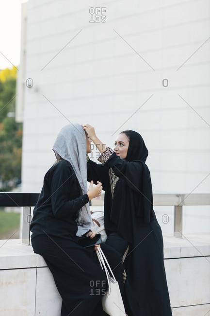 Young Muslim women in burqas talking on city street