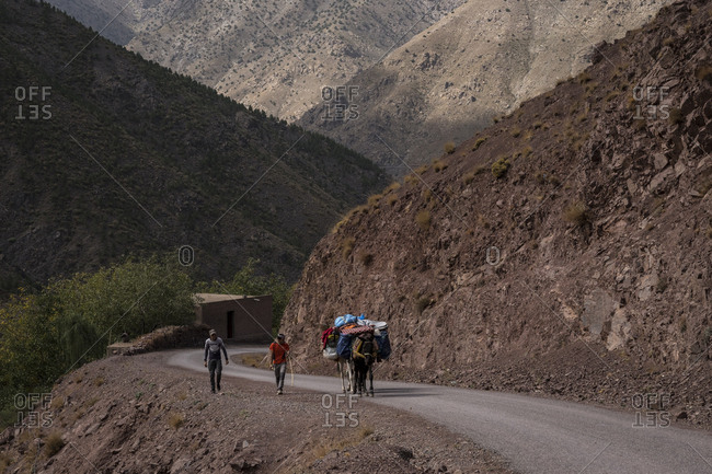 Imlil, Morocco - September 27, 2017: Two men taking a donkey uphill in the Atlas Mountains