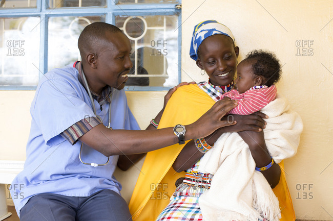 Doctor looking at baby being held by mother at a clinic in Kenya