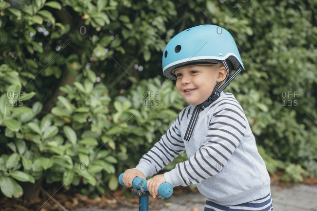 Cute toddler boy riding scooter