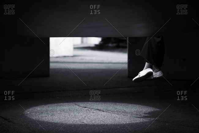 Black and white image of persons feet dangling