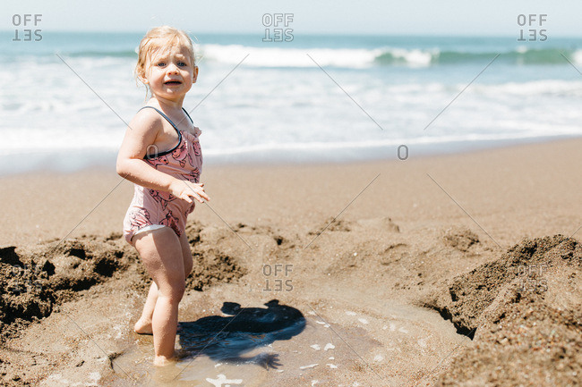 Blonde girl playing in sand on Rodeo Beach, California