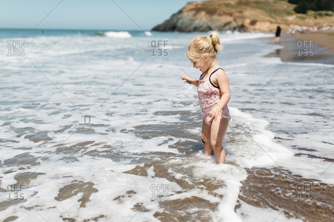 Blonde girl playing in waves, Rodeo Beach, California