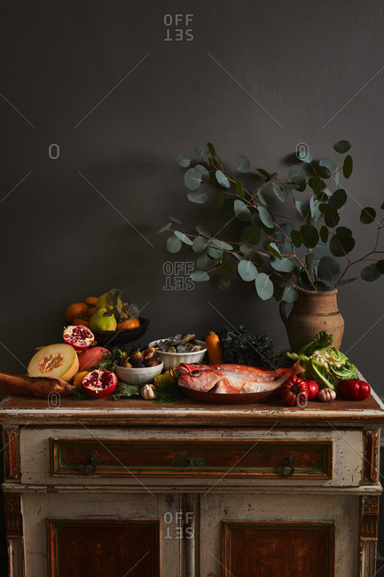 Whole fish served with an abundance of fall produce on an antique table