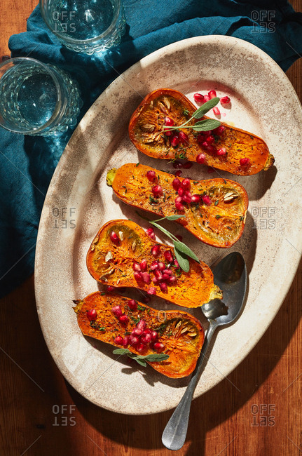 Roasted butternut squash halves garnished with pomegranate seeds and sage