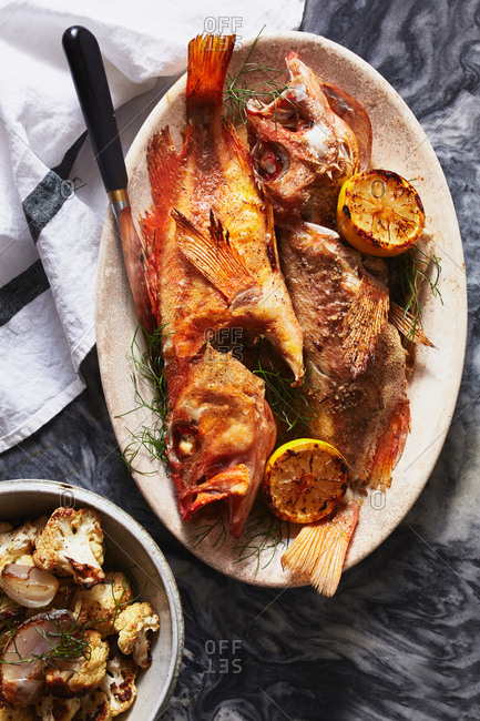 Whole cooked fish served with grilled lemon halves and roasted cauliflower