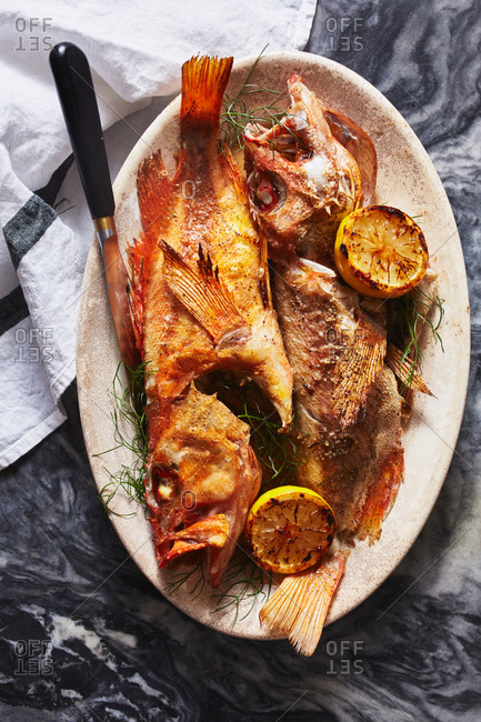 Whole cooked fish served with grilled lemon halves