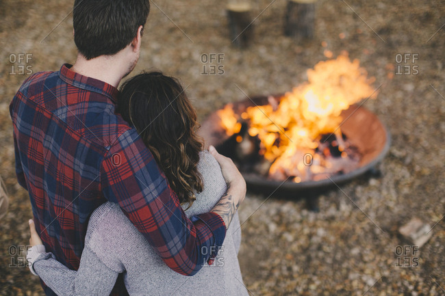 Couple with their arms around each other enjoying an outdoor fire