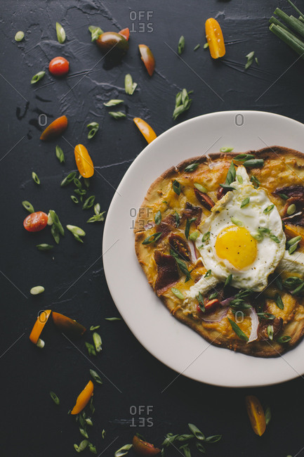 Sunny side up egg served on flat bread breakfast pizza