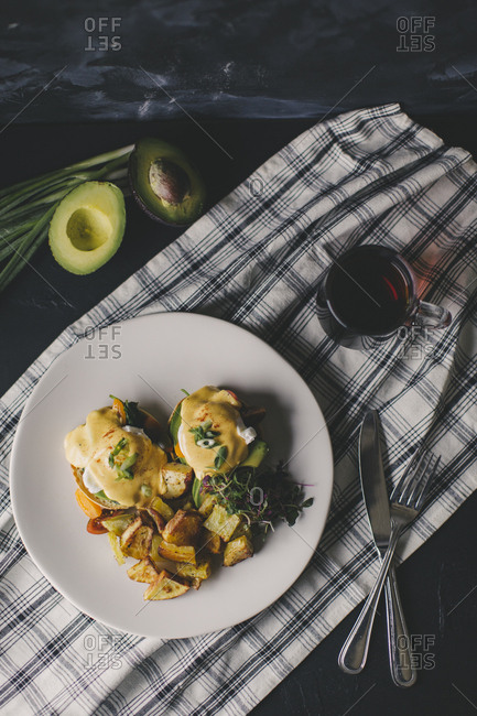 Eggs benedict served with a side of potatoes and an avocado