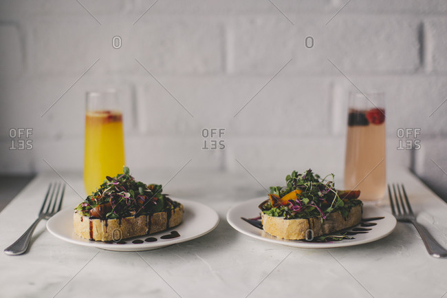 Two plates of toast topped with microgreen salad, tomatoes, and balsamic vinegar served with drinks