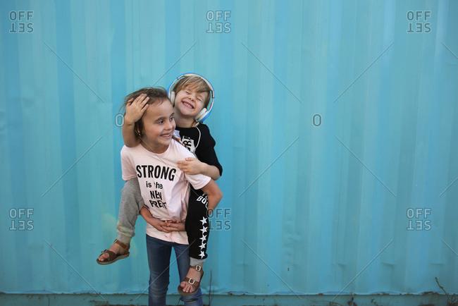 Girl giving little sister a piggy back ride