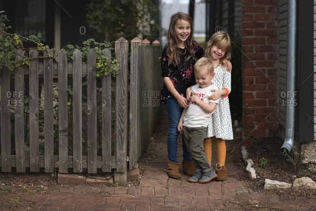Three kids standing together on brick sidewalk smiling