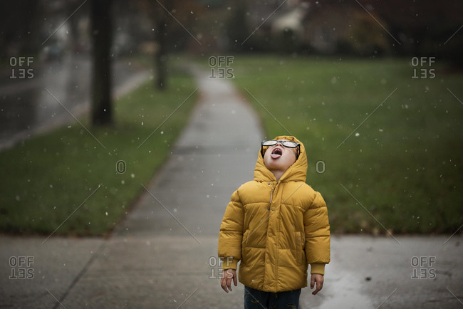 Young boy in yellow jacket catching snowflakes on his tongue