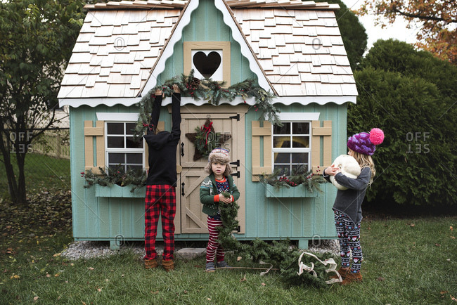 Three children decorating a playhouse for the holidays