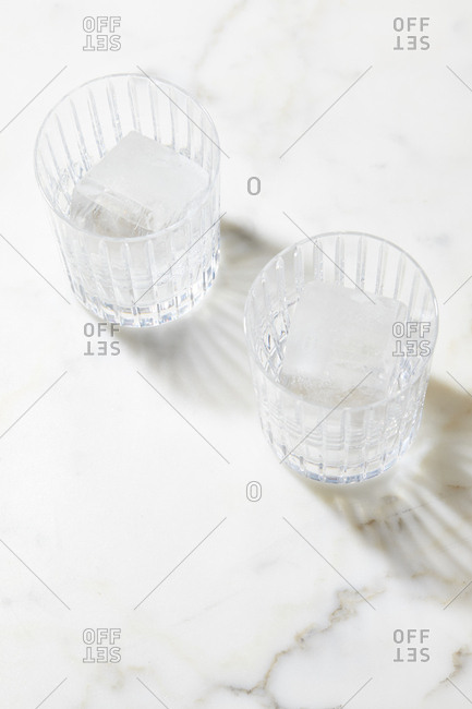 Drinking glasses with ice on marble surface