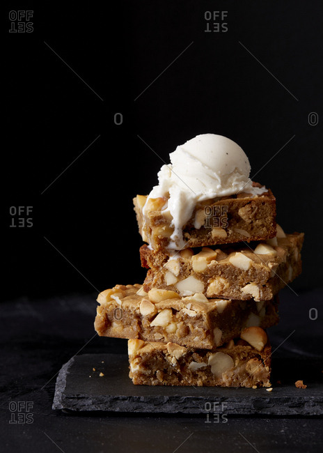 Stack of dessert bars with nuts topped with ice cream