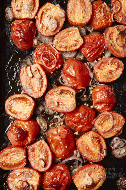 Roasted tomatoes and onion on a baking pan