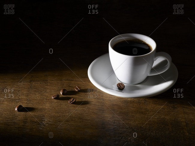 Coffee in coffee cup with beans on wooden table