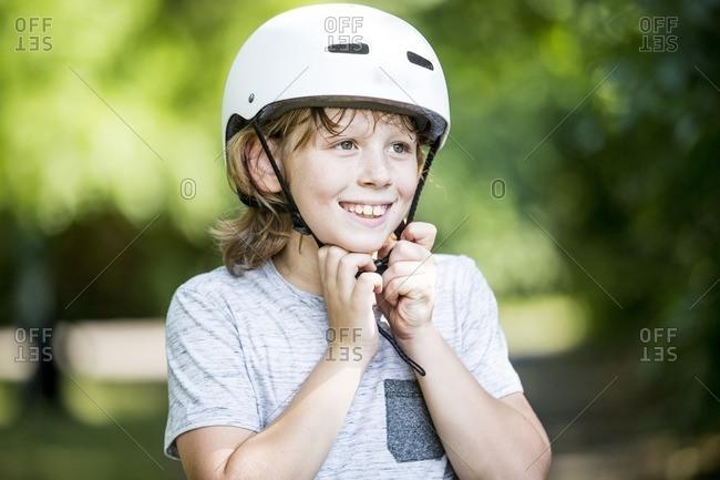 Boy fastening bicycle helmet