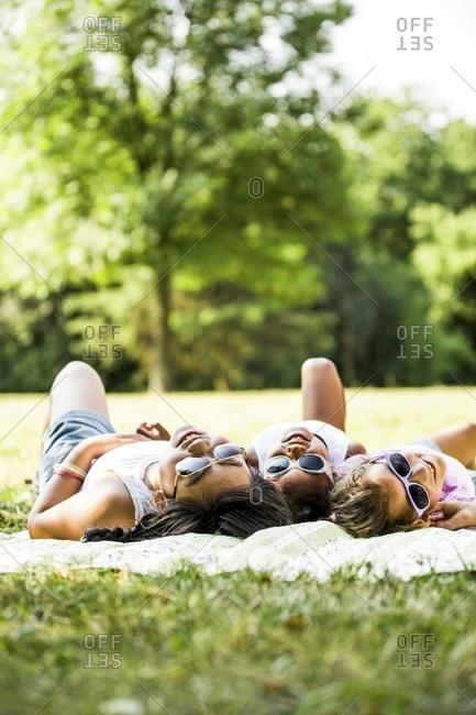 Girls lying on blanket in park