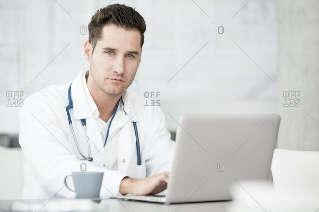 Mature male doctor using laptop