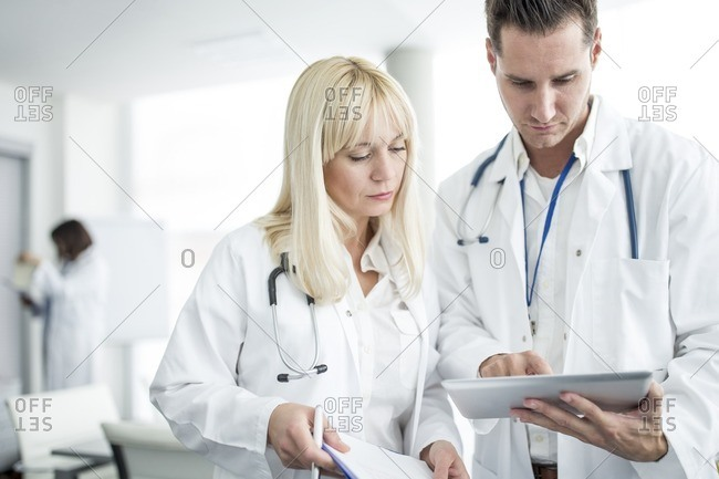 Male and Doctors inspecting digital tablet