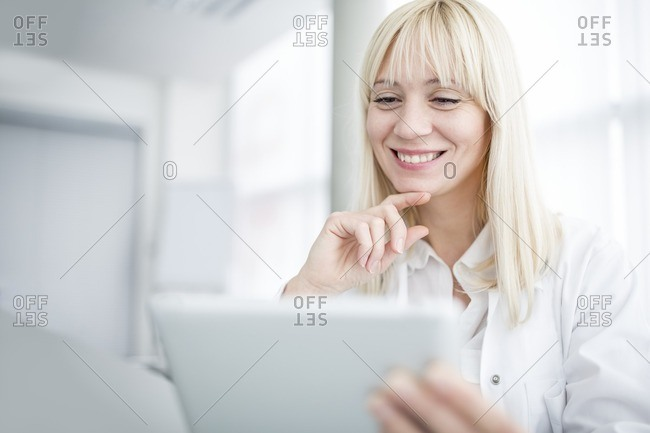 Doctor using tablet and smiling
