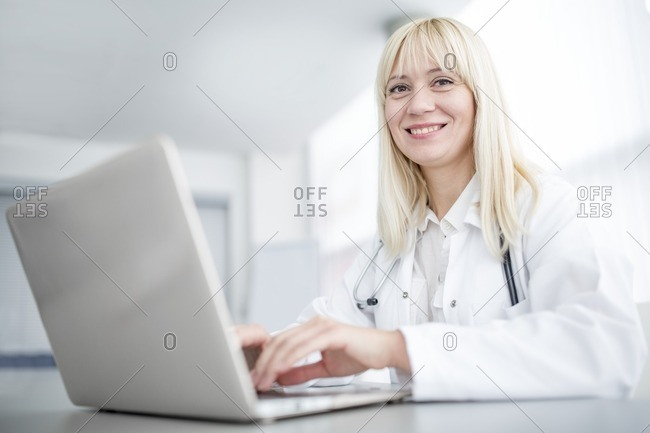Doctor using laptop and smiling