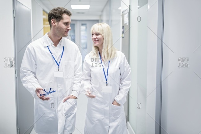 Male and Doctors in white coats walking down corridor