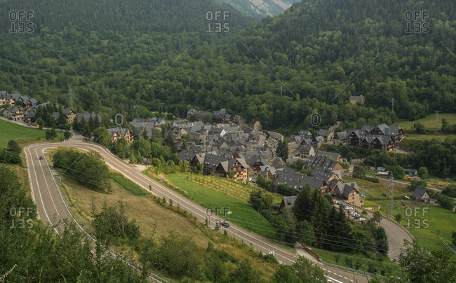 October 2, 2018: Landscape of small town among green trees in valley of Pyrenees mountains with serpentine roadway on slope, Spain