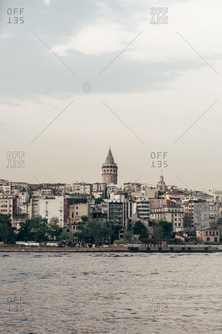 June 4, 2018: Skyline of aged beautiful city at big historic tower and channel with wavy water