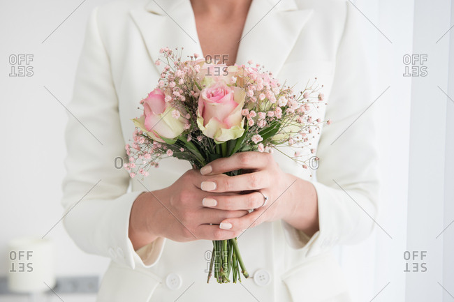Faceless shot of woman in bridal elegant suit holding small bouquet with roses