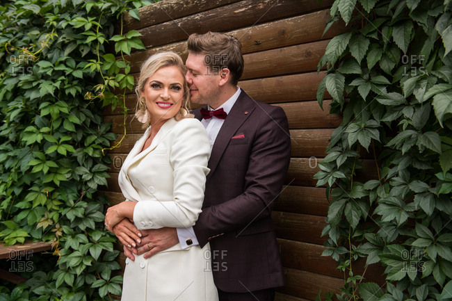 Elegant adult bride and groom embracing while standing in suits against wooden wall and smiling at camera