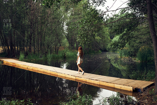 Back view of young woman in dress with long hair walking on wooden bridge above calm smooth river in forest