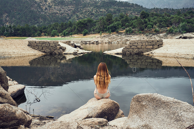 Back view of young woman with long hair in swimming suit sitting on big stone and looking at still lake on background on green trees and mountains