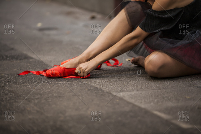 Red head ballerina with black tutu squashing red ballet tips on the street