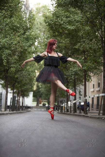 Red head ballerina with black tutu and red ballet tips dancing on the street with trees in the background.