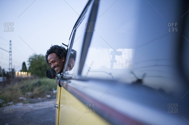 Beautiful afro man enjoys the trip in her vintage van with some friends