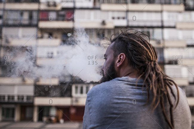 Young and Caucasian Rastafarian man smoking and exposing smoke from behind and look left