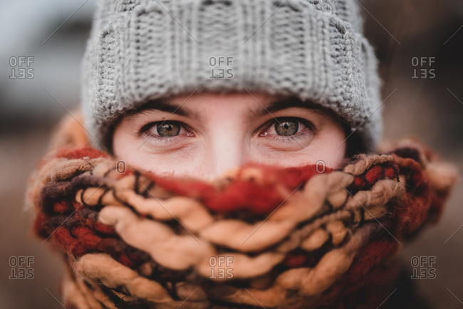 Young beautiful woman in knitted hat and warm scarf pulled on face looking at camera on blurred background