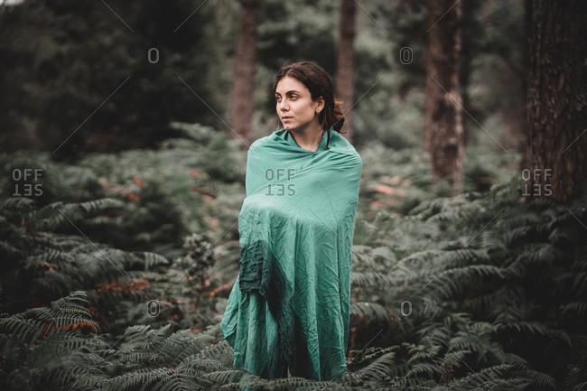 Woman in blanket in forest