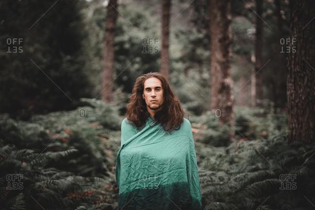 Man in blanket in forest