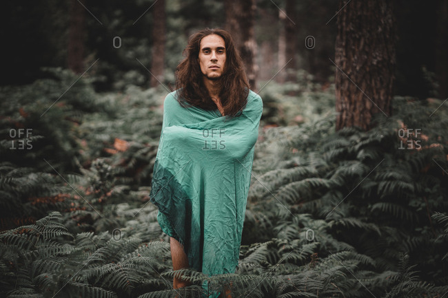 Man in blanket in forest
