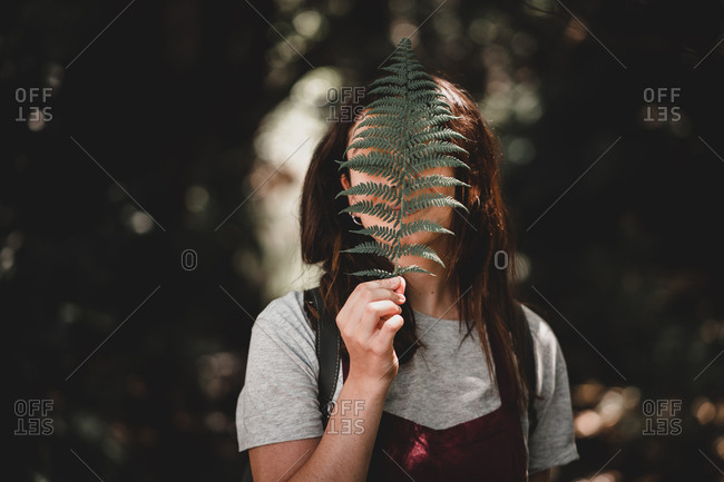 Woman covering face with fern leaf