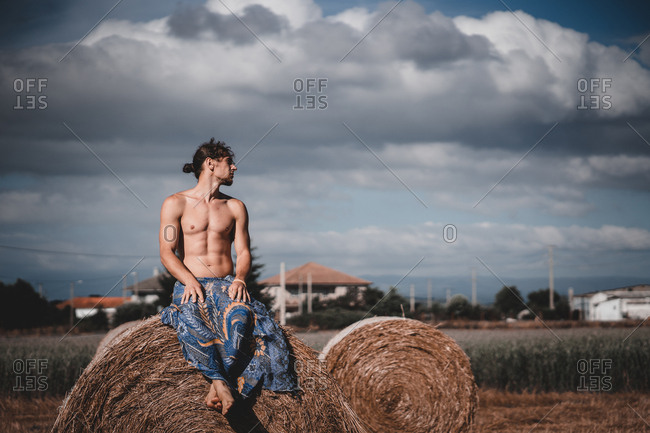 Shirtless man sitting on hay roll